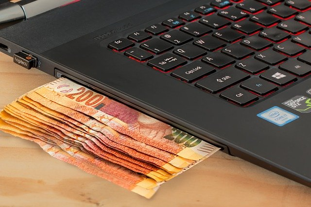 Ecommerce SEO PPC - Money going into laptop for online